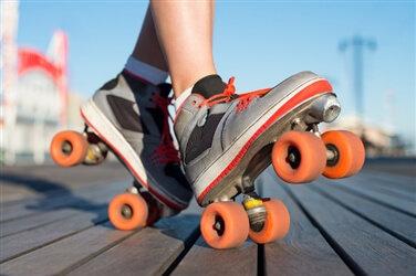 右足の踵を付けて爪先を上げた,オレンジのタイヤが付いたグレーのローラースケート靴