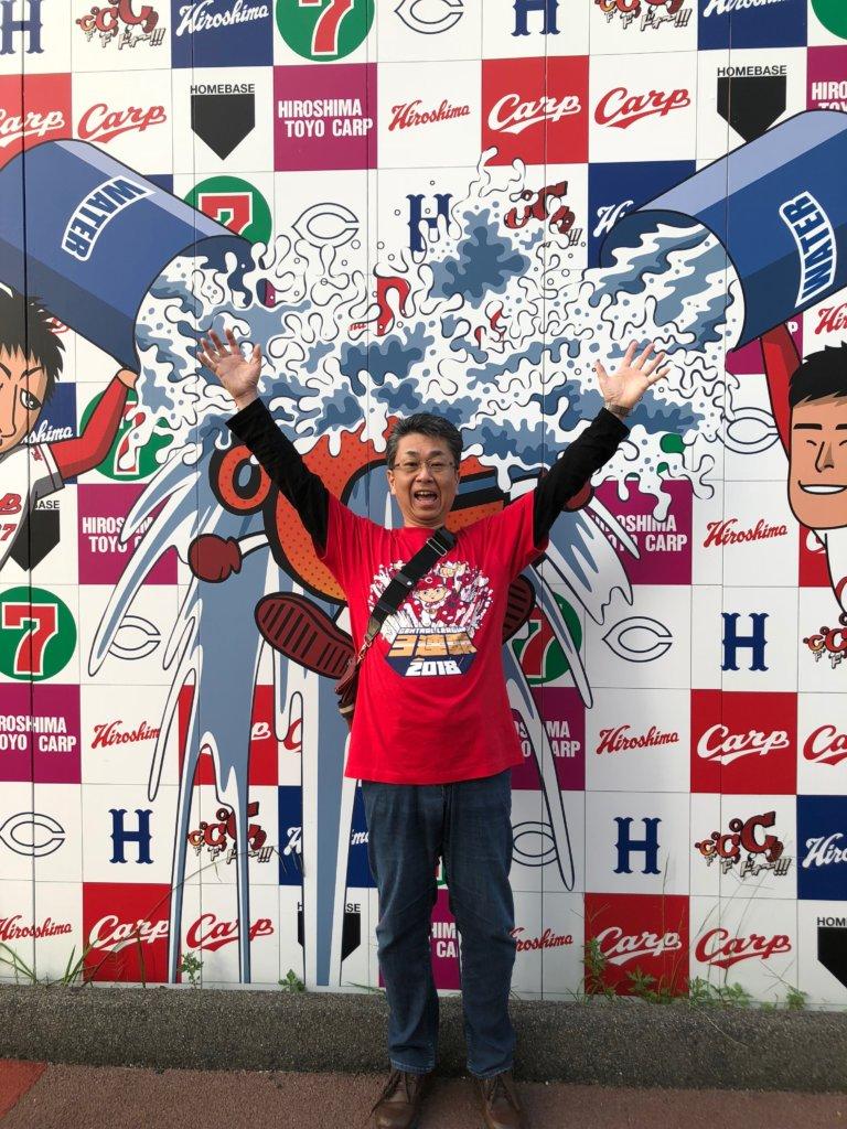2018年日本シリーズ第1戦でカープを応援する前,ヒーローインタビューの水掛けを模したボードの前で万歳をする塾長