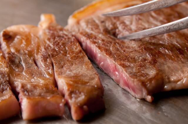 鉄板で焼かれる切れ目の入った高級ステーキ