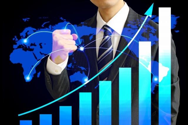 右肩上がりの棒グラフの向こうで自信に満ちた握り拳を胸元で固めるビジネスマン
