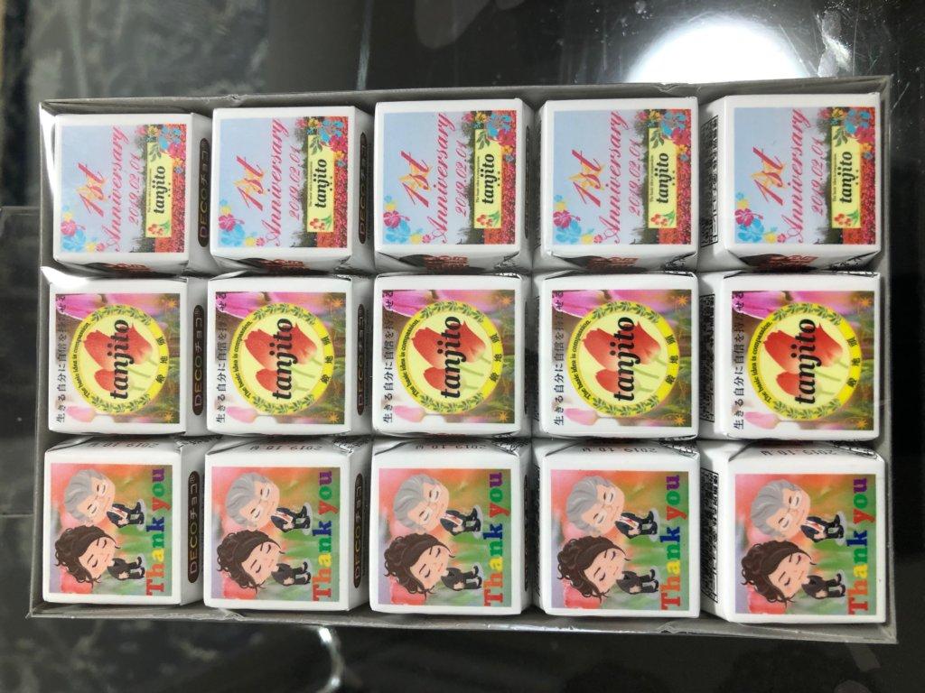 「鍛地頭-tanjito-」のロゴやピグをあしらった包装紙に包まれたバレンタインデーのチロルチョコ群