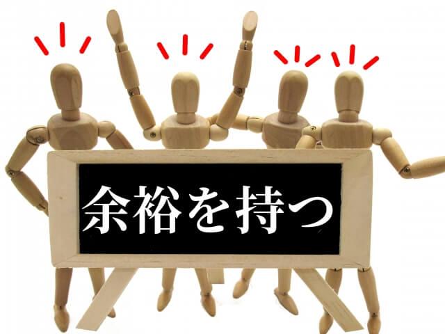 「余裕を持つ」の文字が大書してある木組みの看板の向こうで喧々諤々する4体の木組みの人間たち