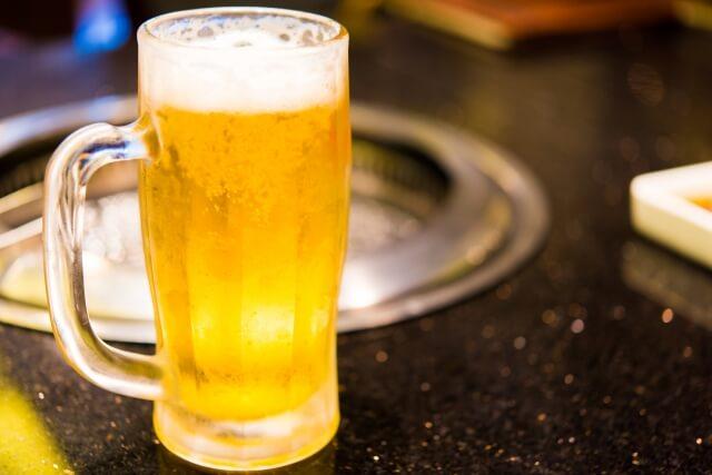 焼き肉屋の七輪の前に置かれた満タンの生ビール