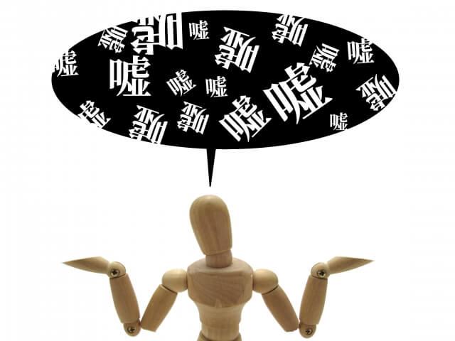 吹き出しの中に数多くの「嘘」の文字。虚言を並べ,恰も本当のように両上でを広げて捲し立てる様子の木製の人形