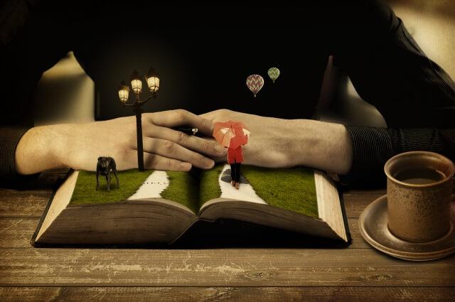 傘をさして歩く女性,犬並びに街灯及び小道のミニチュアで構成される本の世界と読者