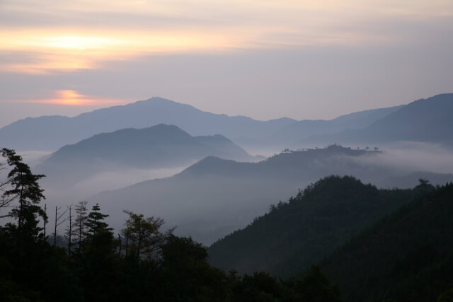 朝靄にぼんやりと浮かぶ山々と雲の中に滲むように昇ってきた朝日