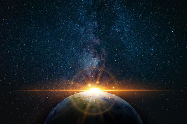 宇宙に浮かぶ地球の輪郭線から昇る太陽