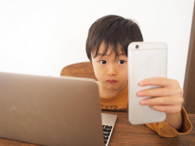 真剣な表情でパソコンとスマホを睨めっこする机に付いた男の子