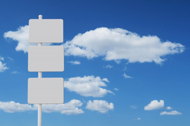 青空と白い雲を背景に白いポールに3択を迫るように掲げられたホワイトボード