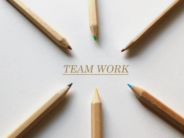 「TEAM WORK」の文字に向けて放射状に配置された6本の色鉛筆