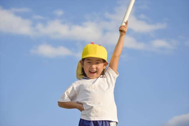 青空を背景に運動会のリレーで使用するバトンを左手で高々と掲げる黄色帽子を被った小学生