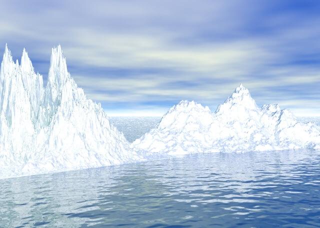 青い空を背景に青い河に鋭く屹立する氷の山