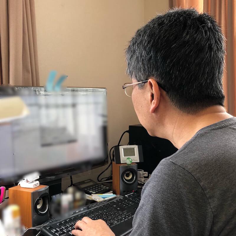 ホームページ作成のため,パソコンとにらめっこをしている男性。